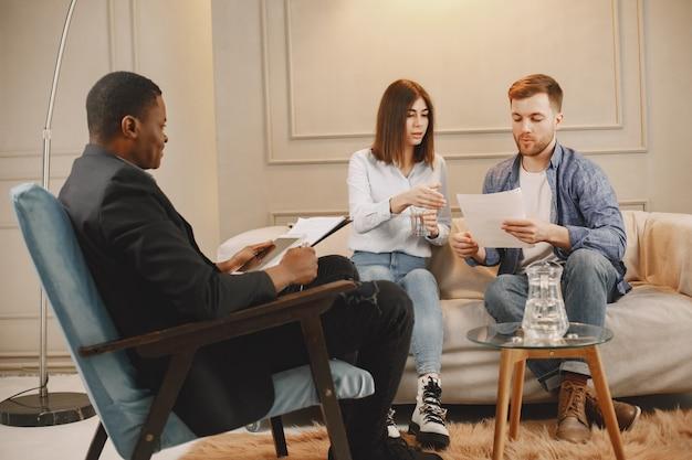 Młoda para w gabinecie psychologa. robią test lub wypełniają koc na terapię.