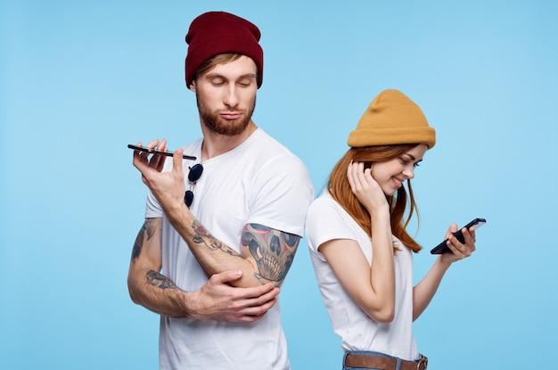Młoda para w kapeluszach z telefonami w rękach komunikacja modowa