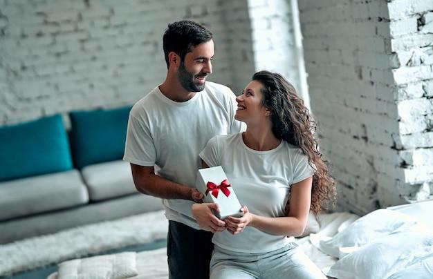 Młoda para w łóżku. atrakcyjny mężczyzna daje prezent swojej szczęśliwej dziewczynie, romans w związku