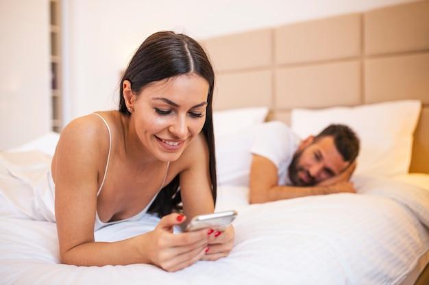 Młoda para w łóżku mąż sfrustrowany zdenerwowany i niezadowolony, gdy jego uzależniona od internetu żona korzysta z telefonu komórkowego w uzależnieniu od sieci społecznościowych