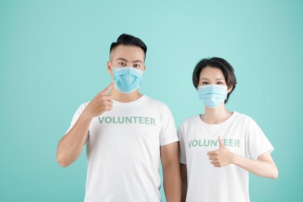 Młoda para w masce medycznej zapraszająca inne osoby do pracy w charakterze wolontariuszy i pomocy ludziom podczas pandemii koronawirusa