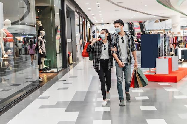 Młoda para w masce ochronnej trzymająca papierową torbę na zakupy idącą korytarzem dużego centrum handlowego