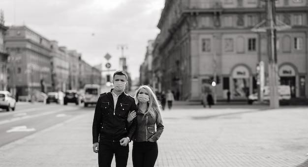 Młoda para w maskach na ulicy miasta. izolacja, kwarantanna.