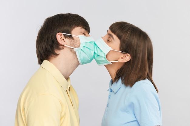 Młoda para w maskach ochronnych całuje się nawzajem, młoda kobieta i mężczyzna całują się na sobie sterylną maskę podczas epidemii