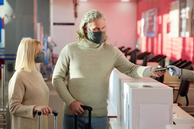 Młoda para w maskach ochronnych stoi z bagażami w recepcji i robi odprawę przed lotem