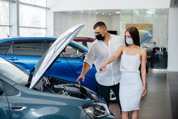 Młoda para w maskach wybiera nowy pojazd i konsultuje się z przedstawicielem dealera w okresie pandemii.