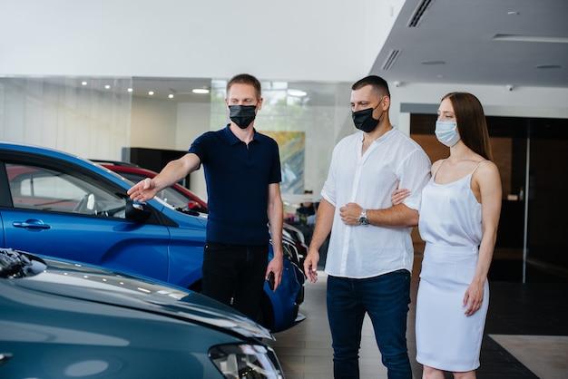 Młoda para w maskach wybiera nowy pojazd i konsultuje się z przedstawicielem salonu w okresie pandemii. sprzedaż samochodów i życie w czasie pandemii.