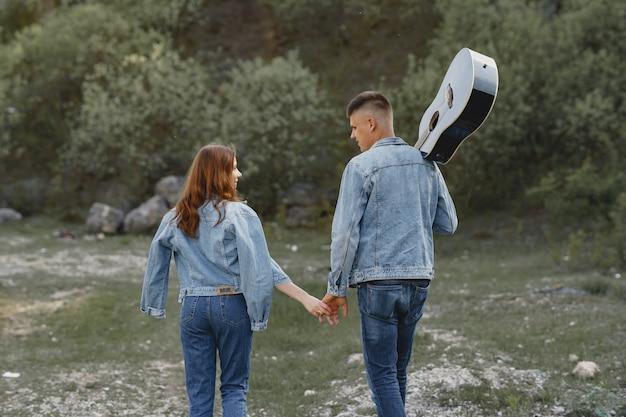 Młoda para w miłości, chłopak trzyma gitarę