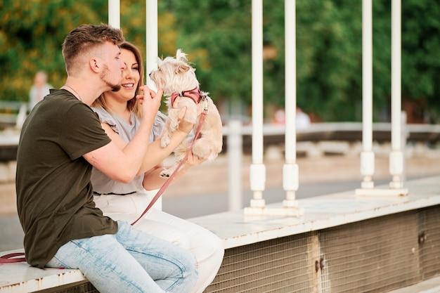 Młoda para w moście z psem w scenie miejskiej