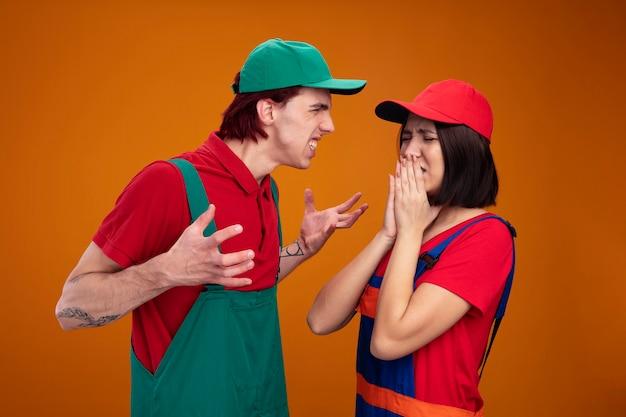 Młoda para w mundurze pracownika budowlanego i czapce agresywny facet patrzący na dziewczynę rozkładającą ręce przestraszona dziewczyna trzymająca ręce na ustach z zamkniętymi oczami