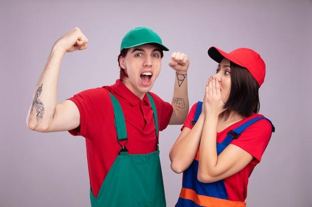 Młoda para w mundurze pracownika budowlanego i czapce pewny siebie facet robi silny gest zaniepokojona dziewczyna trzymająca ręce na ustach patrząca na faceta