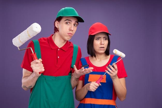 Młoda para w mundurze pracownika budowlanego i czapce trzymającej wałek do malowania nieświadomy facet patrzący na kamerę pokazującą pustą rękę zdezorientowaną dziewczynę patrzącą na jej wałek do malowania odizolowaną na fioletowej ścianie