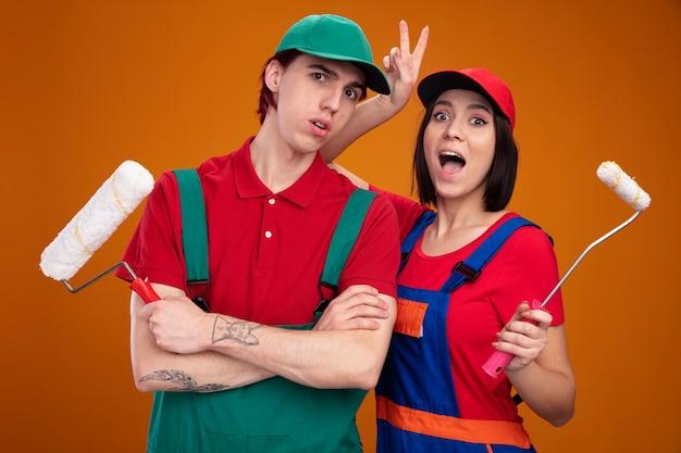 Młoda para w mundurze pracownika budowlanego i czapce trzymającej wałek do malowania zaskoczony facet stojący z zamkniętą postawą podekscytowana dziewczyna robiąca uszy królika za głową facetów