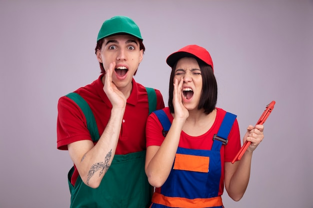 Młoda para w mundurze pracownika budowlanego i czapce wściekła dziewczyna trzymająca klucz do rur krzycząca głośno z zamkniętymi oczami podekscytowany facet oboje trzymający rękę w pobliżu ust odizolowany