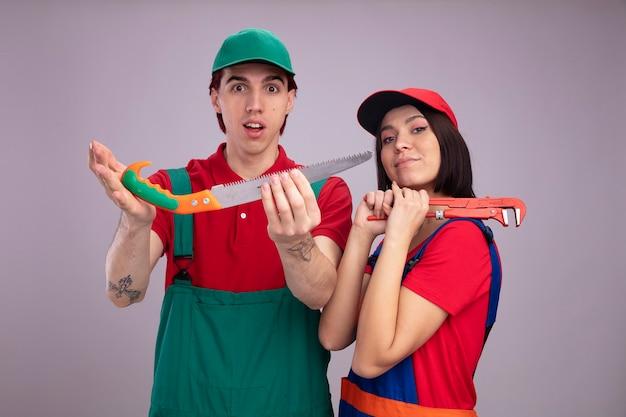 Młoda para w mundurze pracownika budowlanego i czapce zadowolona dziewczyna stojąca w widoku profilu trzymając klucz do rur na ramieniu pod wrażeniem facet wyciągający ręczną piłę