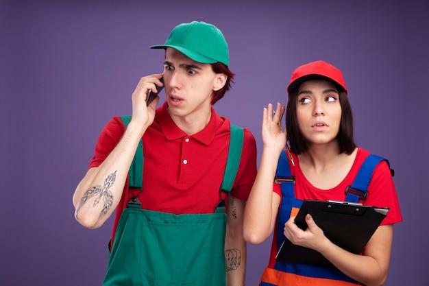 Młoda para w mundurze pracownika budowlanego i czapce zaniepokojony facet rozmawia przez telefon patrząc w dół ciekawa dziewczyna trzyma ołówek i schowek patrząc z boku słuchając rozmowy telefonicznej na białym tle