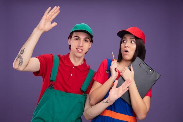 Młoda para w mundurze pracownika budowlanego i czapce zaskoczona dziewczyna trzyma ołówek i schowek, patrząc na bok zadowolony facet podnoszący rękę
