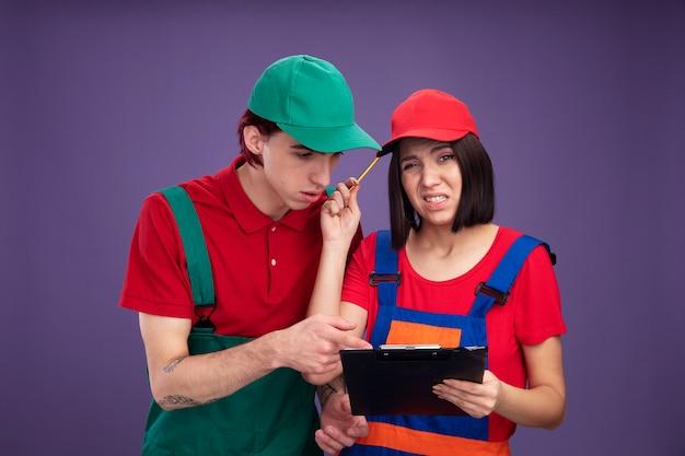 Młoda para w mundurze pracownika budowlanego i czapce zdezorientowana dziewczyna trzymająca ołówek i schowek dotykająca głowy ołówkiem skoncentrowany facet patrząc i wskazując na schowek na białym tle