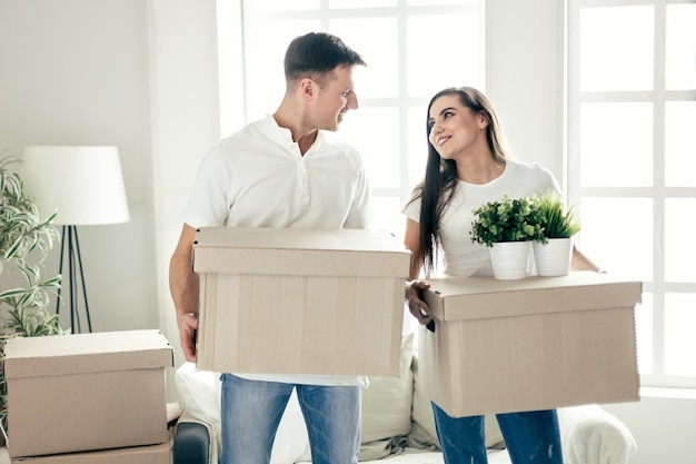 Młoda para w nowym mieszkaniu z kartonami