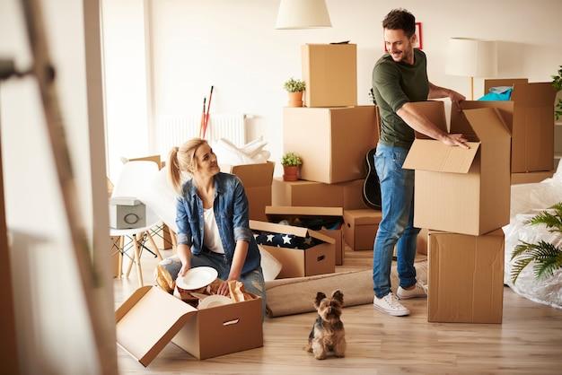 Młoda para w nowym mieszkaniu z małym psem