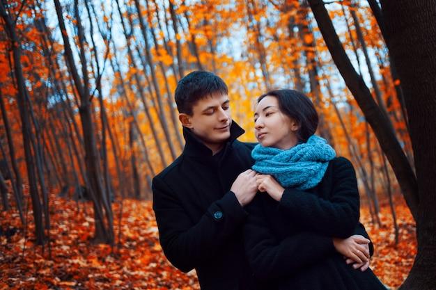 Młoda para w parku jesień. uroczy facet i dziewczyna idą razem