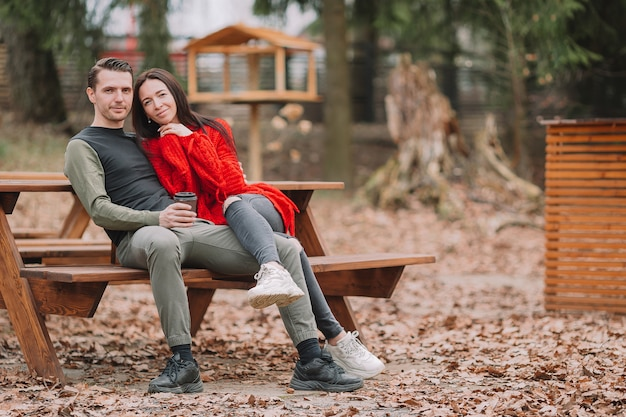 Młoda para w parku na świeżym powietrzu przy autentycznym stole w kawiarni
