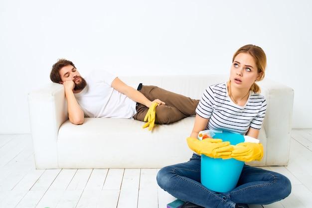 Młoda para w pobliżu sofy do czyszczenia dostarcza jasne tło