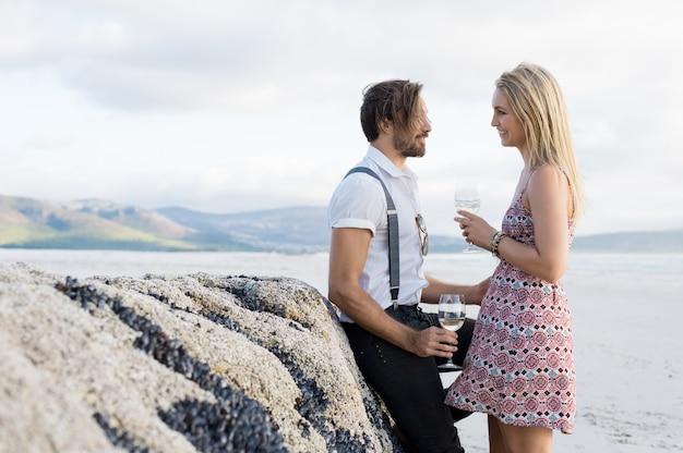 Młoda para w rozmowie przy lampce białego wina