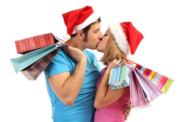 Młoda para w santa kapeluszach robi zakupy i trzyma wiele toreb na zakupy na białym tle