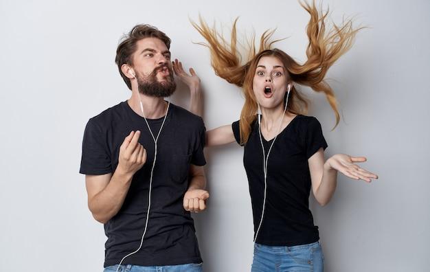 Młoda para w słuchawkach technologia muzyka studio na białym tle zabawa