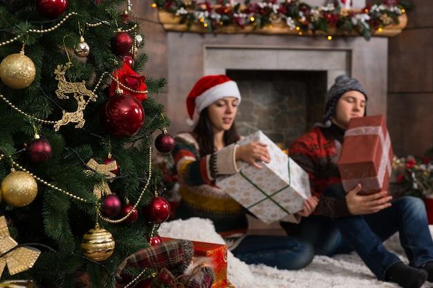 Młoda para w śmiesznych czapkach i swetrach siedzi na dywanie przed udekorowanym kominkiem i choinką rozpakowując świąteczne prezenty