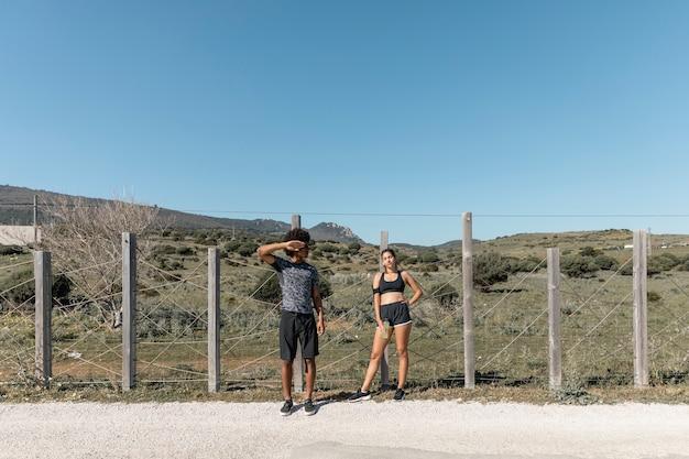 Młoda para w sportowej stoi na poboczu drogi