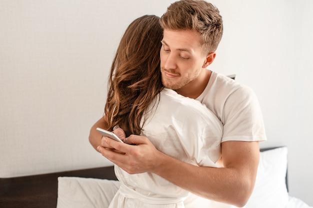 Młoda para w sypialni. uśmiechnięty niewierny mężczyzna oszukuje i pisze sms-a przez telefon, jednocześnie przytulając swoją dziewczynę
