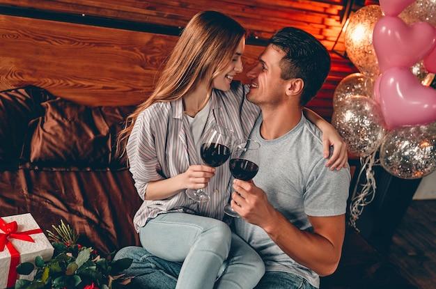 Młoda para w sypialni z kieliszkami wina, prezentem i czerwonymi różami. walentynki. rocznica. urodziny.