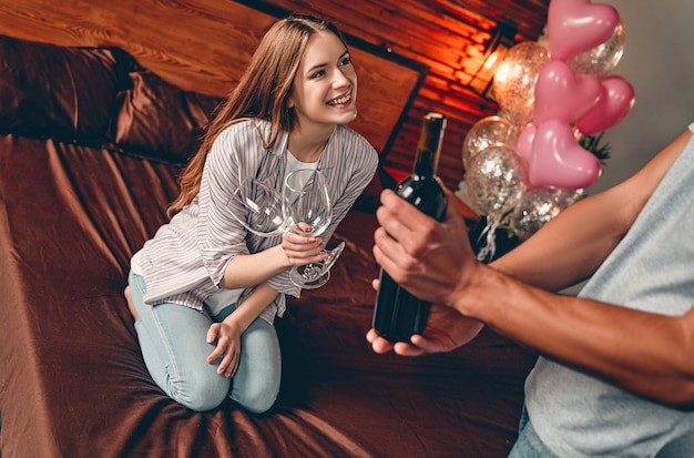 Młoda para w sypialni z okularami i winem. walentynki. rocznica. urodziny.
