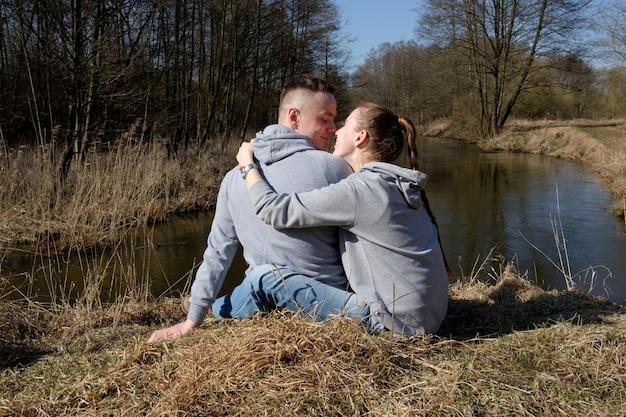 Młoda para w szarych bluzach i dżinsach siedzi na brzegu leśnej rzeki, przytulając się i uśmiechając.