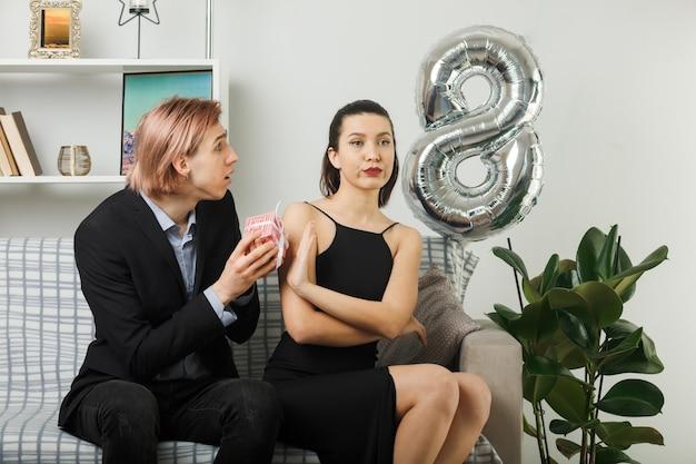 Młoda para w szczęśliwy dzień kobiet smutny facet daje prezent surowej kobiecie siedzącej na kanapie w salonie