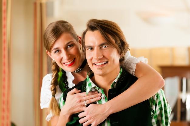 Młoda para w tradycyjnym bawarskim tracht w restauracji lub pubie