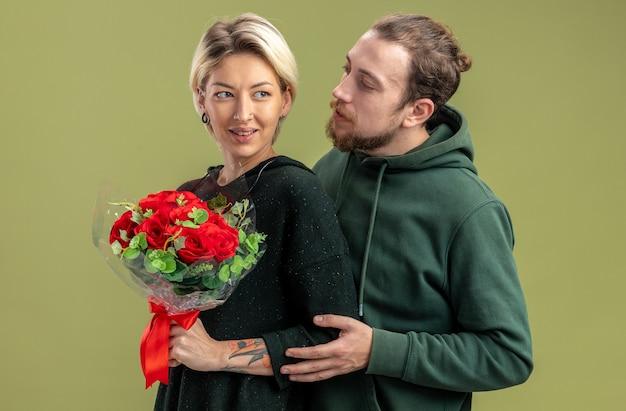 Młoda para w ubranie szczęśliwy mężczyzna obejmujący swoją piękną kobietę z kwiatami świętuje walentynki stojąc nad zieloną ścianą