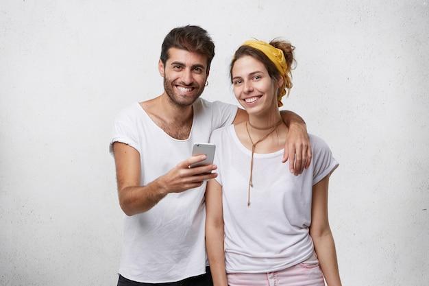 Młoda para w ubranie za pomocą smartfona w studio