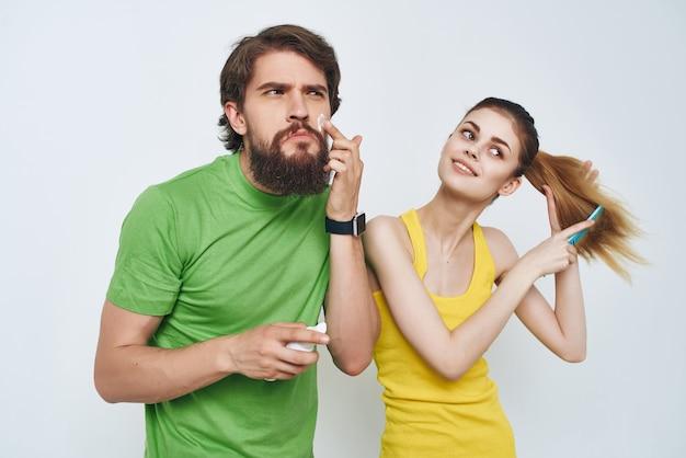 Młoda para w wielobarwne koszulki higiena pielęgnacja twarzy zdrowy poranek. zdjęcie wysokiej jakości