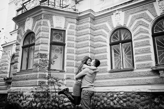 Młoda para w zakochanych ciepłych swetrach. dziewczyna dziewczyna na szyi swojego chłopaka. kochanka tła stary budynek na mieście.