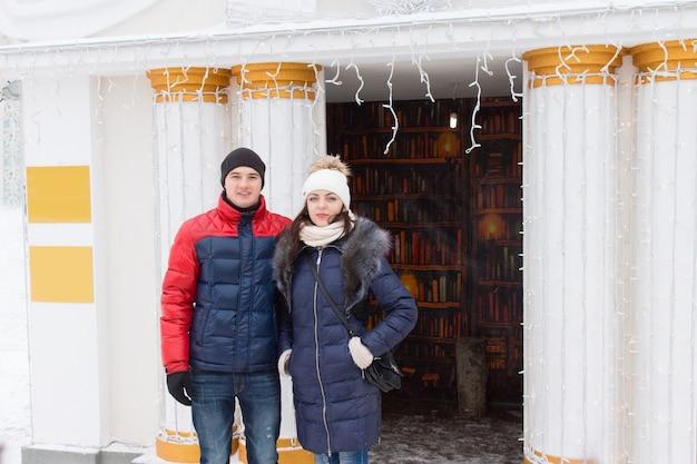 Młoda para w zimowych strojach pozuje na zewnątrz przed ozdobnymi białymi kolumnami otaczającymi wejście ozdobione girlandą małych imprez lub lampek choinkowych
