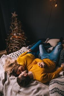 Młoda para w żółtych swetrach leżąca na łóżku w pobliżu choinki
