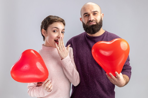 Młoda para w zwykłych ubraniach mężczyzna i kobieta trzymający balony w kształcie serca patrząc w kamerę szczęśliwi i zaskoczeni świętując walentynki stojąc nad białą ścianą