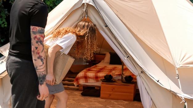 Młoda para wchodzi do namiotu na glamping trzymając się za ręce. zieleń wokół