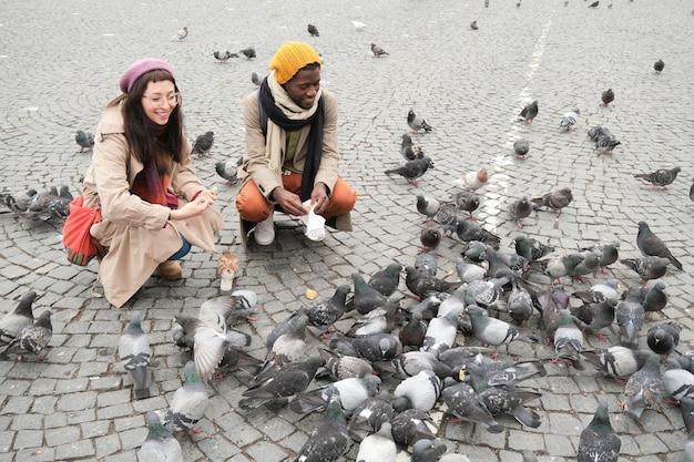 Młoda para wieloetniczna spacerująca razem na świeżym powietrzu, karmiąca ptaki