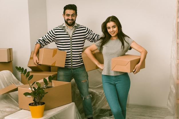 Młoda para wprowadza się do nowego domu z dużą ilością pudeł