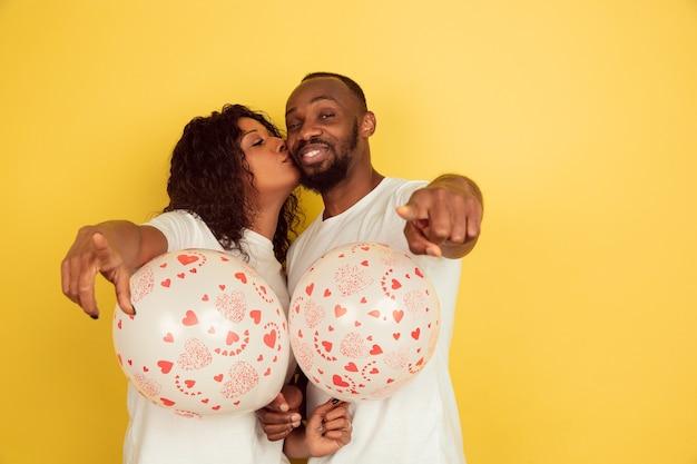 Młoda para wskazuje z balonami