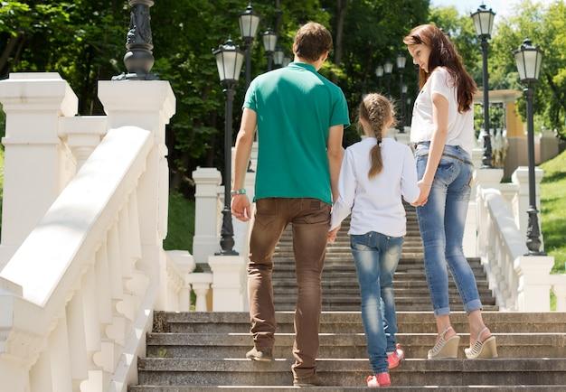Młoda para wspina się po schodach z małą dziewczynką